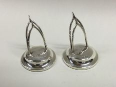 A pair of silver menu holders in the form of wishb
