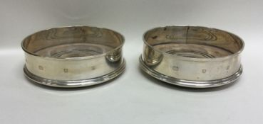A pair of silver wine coasters with mahogany inset