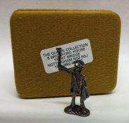 A novelty miniature silver figure of a paper selle