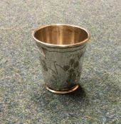 An engraved silver beaker of tapering form decorat
