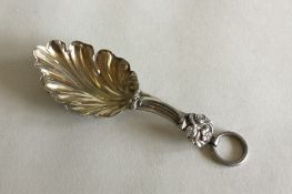 An Antique silver caddy spoon with leaf decoration