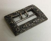 A heavy cast silver buckle of Eastern design decor