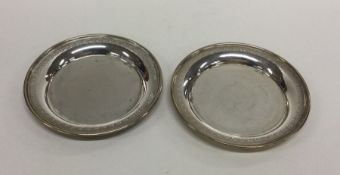 A pair of circular engraved silver dishes. 800 Sta