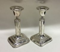 A pair of Edwardian silver candlesticks with reede