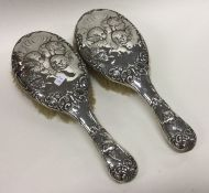 A pair of heavy silver brushes decorated with cher