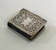 A small silver mounted book with embossed decorati