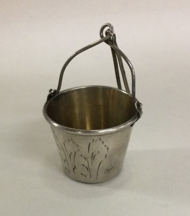 A tapering Russian silver tea strainer with gilt h
