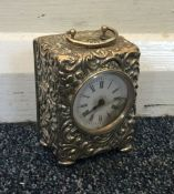 An embossed silver carriage clock on four bun feet