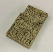 A carved ivory card case profusely decorated with