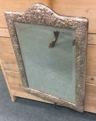 A massive silver mounted mirror decorated with scr
