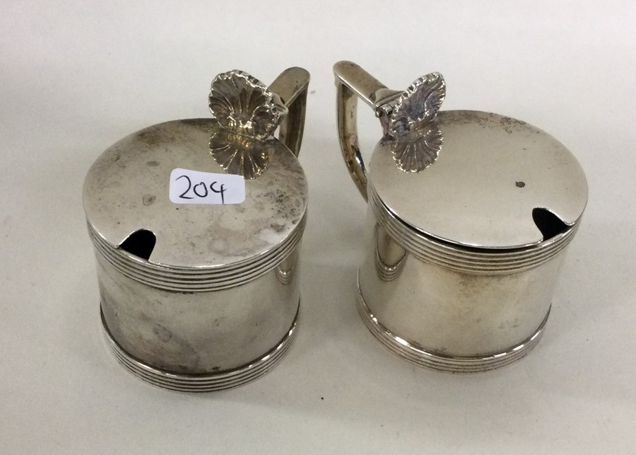 A pair of Edwardian silver mustard pots with shell