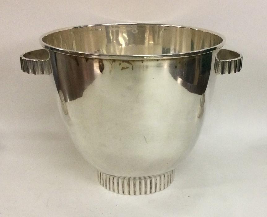 A stylish silver ice bucket on pedestal base. Appr