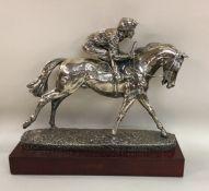 A good silver figure of a jockey on horseback on w