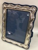 A large silver mounted picture frame with shaped d
