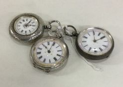 A group of three silver fob watches with white ena