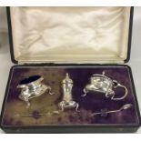 A cased silver three piece cruet set of circular f
