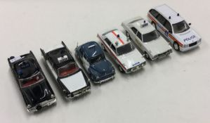VANGUARDS: A toy police car together with five oth