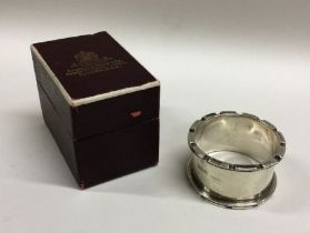 A heavy silver napkin ring contained within a fitt