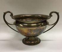 A heavy Edwardian silver two handled cup on spread