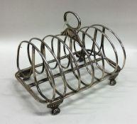 A heavy Georgian silver toast rack on reeded taper