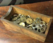 A wooden box containing assorted clockwork gears. Est. £5 - £10.