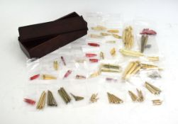 A 19th century mahogany box containing a group of bone and brass marker pegs together with a