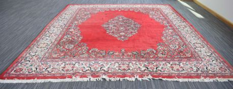 A Persian woolen carpet, the bright red ground with a central floral medallion and matching bands,