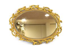 A 19th century wall mirror, the oval bevelled plate within a giltwood foliate fretwork frame,