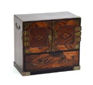 An Oriental marquetry cabinet, the two doors with brass hinges enclosing six drawers,