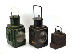 A BR(M) railway lantern together with a similar green lantern and a smaller light