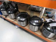 4 unboxed instant pots and a pressure cooker