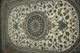 An Iranian carpet, the beige and blue ground with a central medallion,