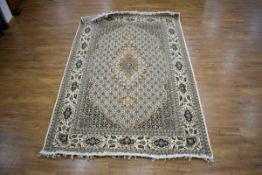 An Iranian carpet, the beige and blue ground with repeated diamond motifs,