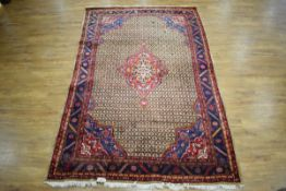 An Iranian carpet, the brown, red and blue ground with repeated diamond motifs and abstract bands,