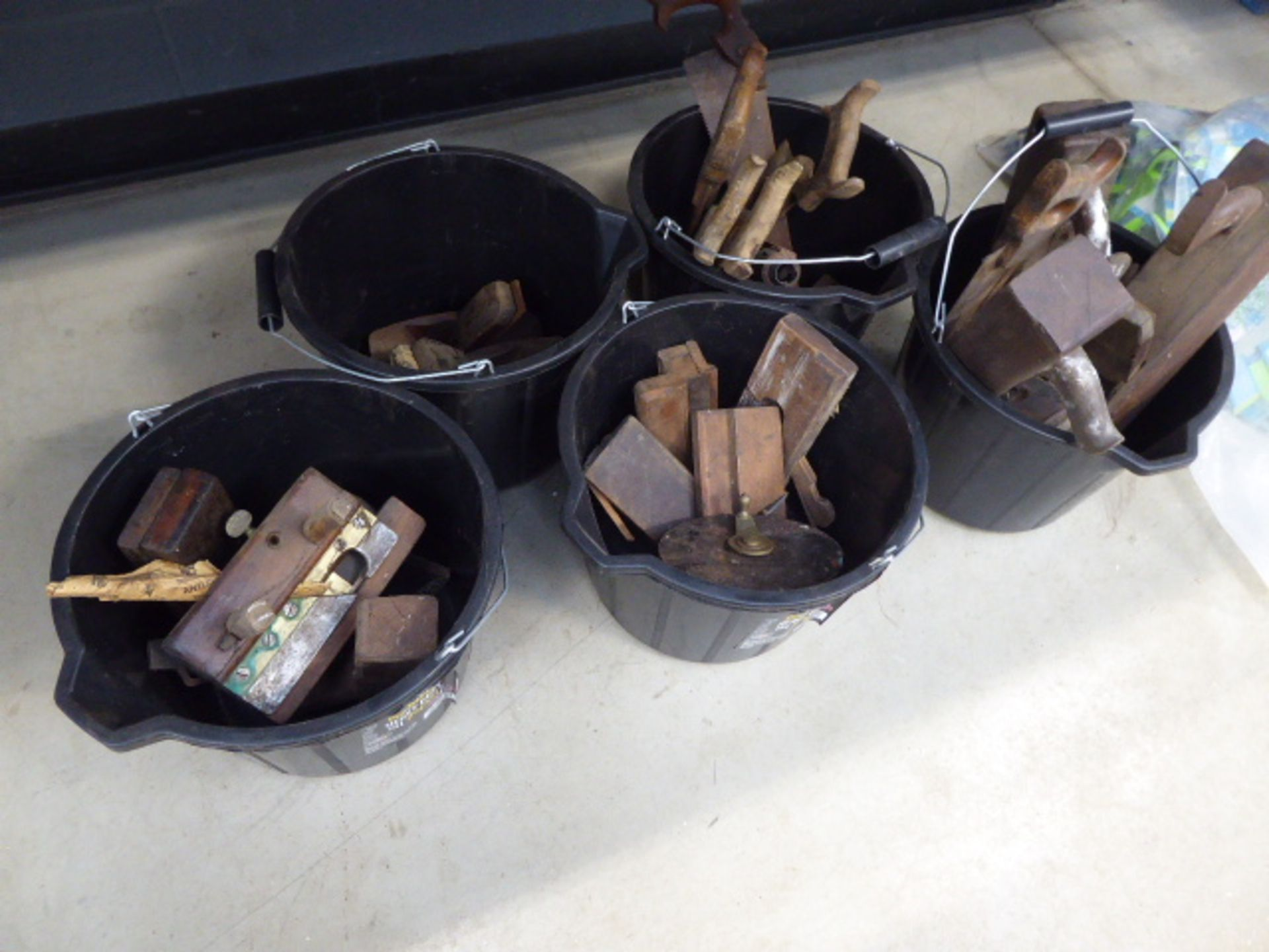 5 buckets containing wood chisels, blow lamps, vintage saws, tape measuring tape, etc.