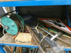 Shelf containing a hose reel and hose, boule set, garden tools, tennis racket, seed spreader and