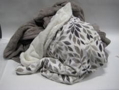 Bag containing large beige coloured throw with cream and leaf decorated throw