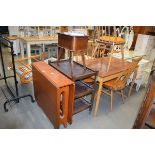 A 1970's tea drop leaf dining table, an oak three tier tea trolley and a mid 20th century sewing