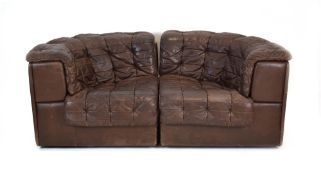 A 1970's De Sede brown leather two-section modular sofa on a mahogany plinth base *Sold subject to