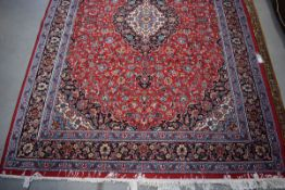 (11) An Iranian Pamchal carpet, red ground and blue border with Persian style foliate decoration