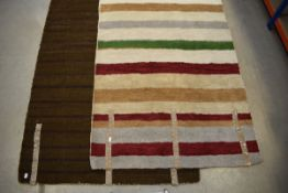 A brown 1970's carpet and a similar stripy coloured carpet Would benefit from a clean. Holes and