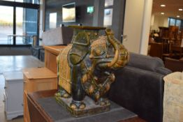 Green glazed ceramic garden seat in the form of an elephant Grazing to glaze and some losses