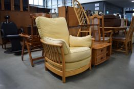 Ercol elm single armchair with loose cream upholstered cushions Some discolouration to cushions.