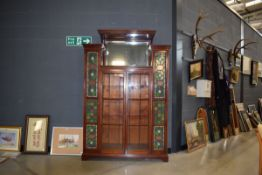 Late 19th/ Early 20th Century glazed mahogany cabinet in the arts and crafts manner, having pair
