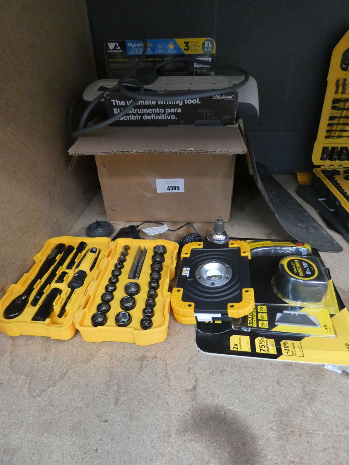 Box containing work gloves, extension cable, small DeWalt socket set, Stanley FatMax tape measure