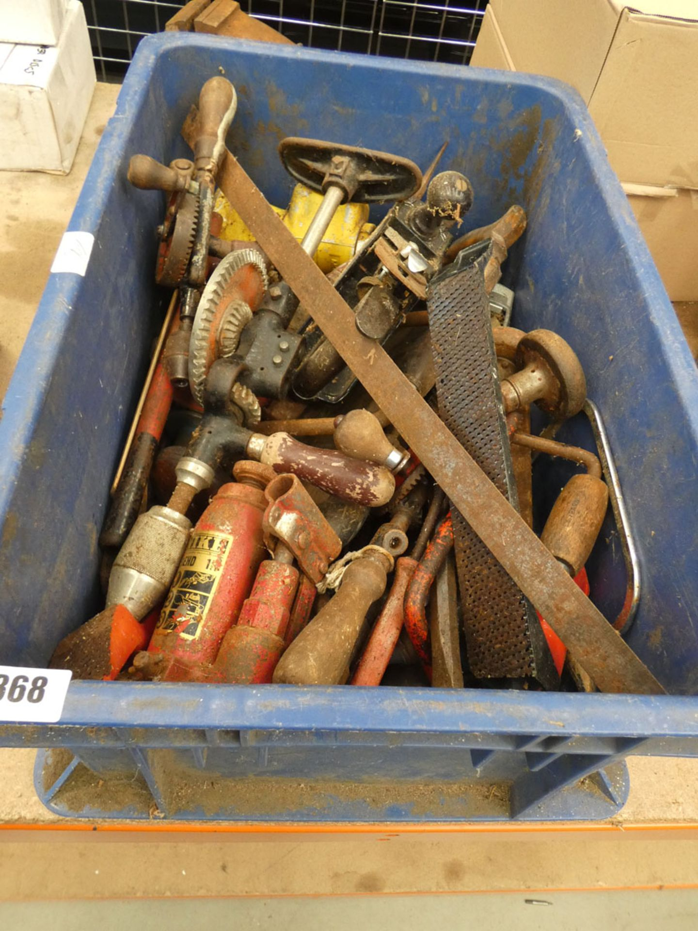 Large blue box containing hand drill, bottle jack and planes etc