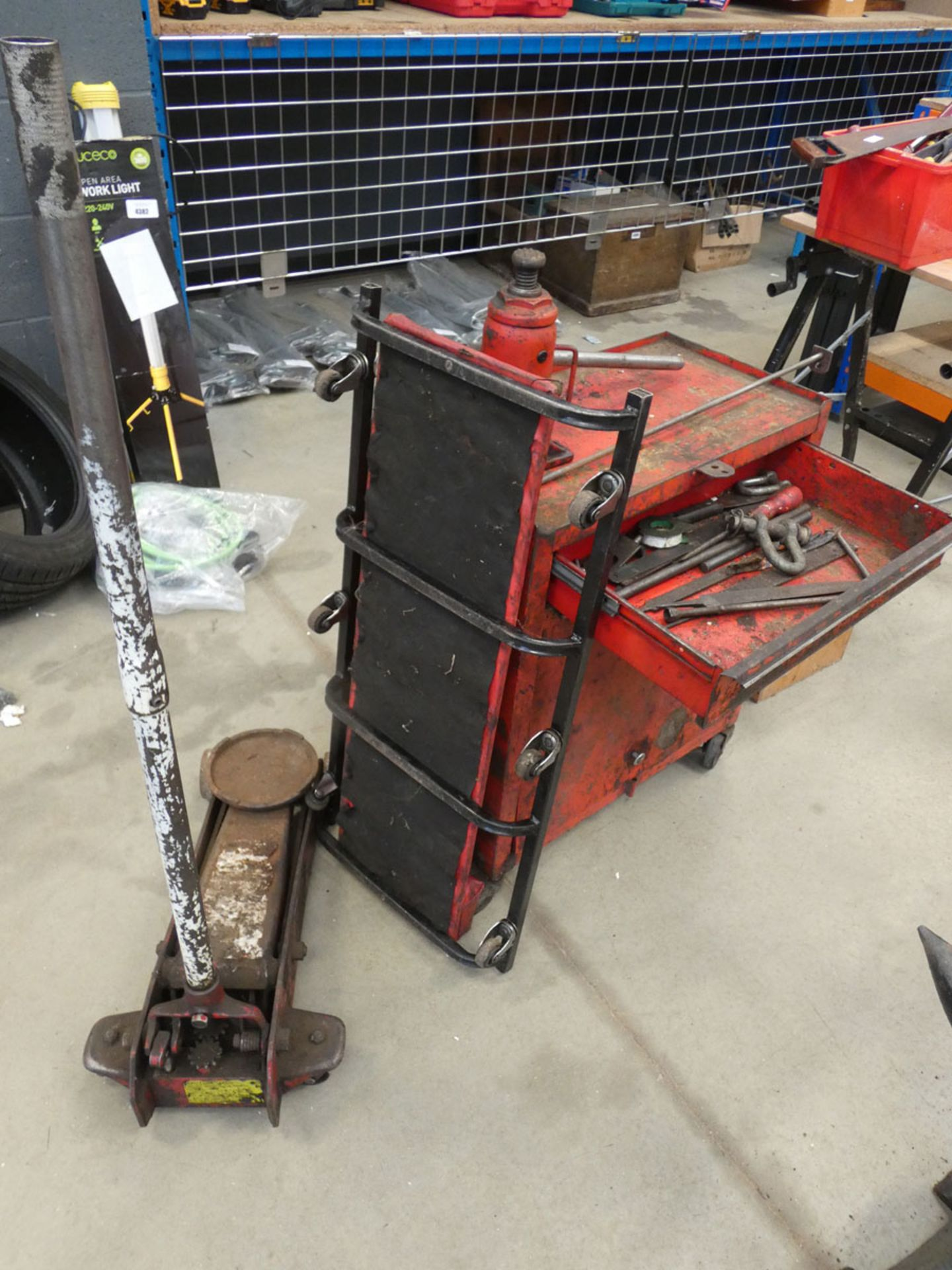 Red 4 wheeled toolbox, bottle jack, trolley jack and a mechanics creeper board