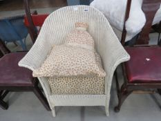 Cream Lloyd Loom armchair with cushion and lampshade