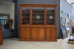 Glazed Victorian oak panelled three-door library bookcase with storage cupboards under and