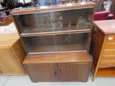 Dark beech and glazed bookcase with sliding doors and cupboard under In good condition for it's age